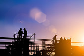 istock Silhouette of engineer and construction team working at site over blurred background for industry background with Light fair.Create from multiple reference images together 1052879992