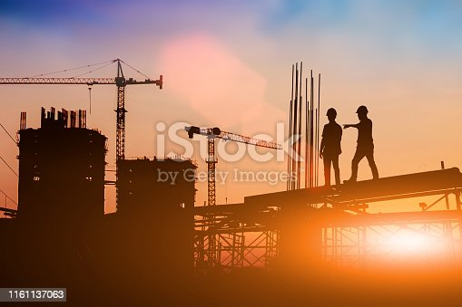 istock Silhouette of engineer and construction team working at site over blurred background for industry background with Light fair.Create from multiple reference images together 1161137063