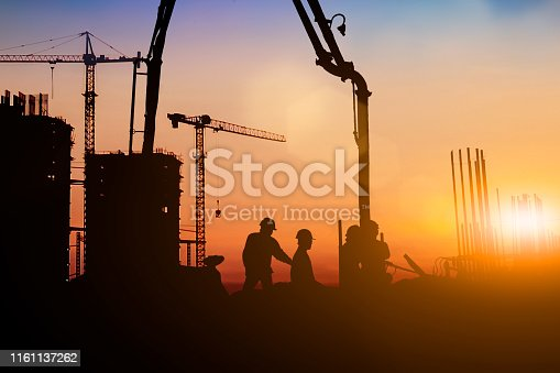 istock Silhouette of engineer and construction team working at site over blurred background for industry background with Light fair.Create from multiple reference images together 1161137262