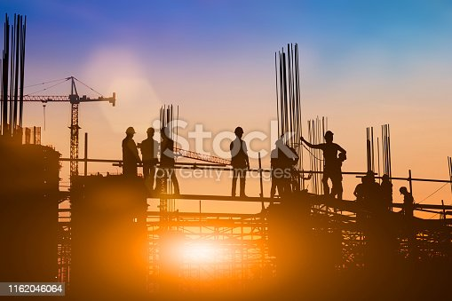 istock Silhouette of engineer and construction team working at site over blurred background for industry background with Light fair.Create from multiple reference images together 1162046064