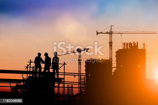 istock Silhouette of engineer and construction team working at site over blurred background for industry background with Light fair.Create from multiple reference images together 1162046065