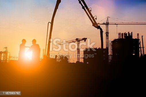 istock Silhouette of engineer and construction team working at site over blurred background for industry background with Light fair.Create from multiple reference images together 1182593762