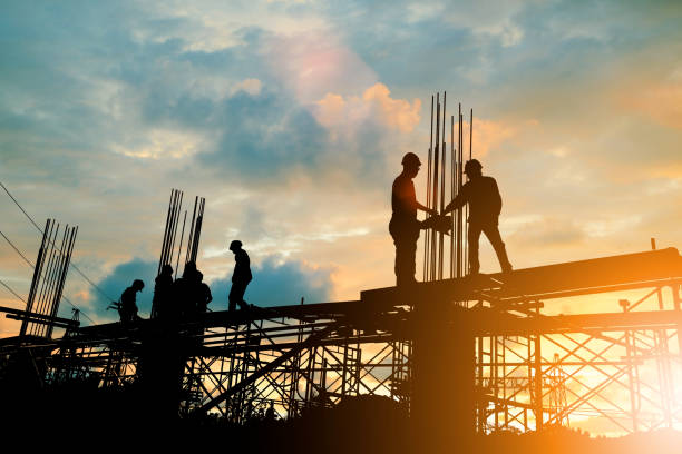 Silhouette of engineer and construction team working at site over blurred background sunset pastel for industry background with Light fair.Create from multiple reference images together. Silhouette of engineer and construction team working at site over blurred background sunset pastel for industry background with Light fair.Create from multiple reference images together. built structure stock pictures, royalty-free photos & images
