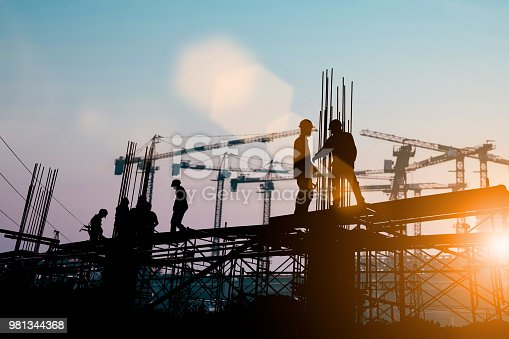 istock Silhouette of engineer and construction team working at site over blurred background sunset pastel for industry background with Light fair.Create from multiple reference images together. 981344368