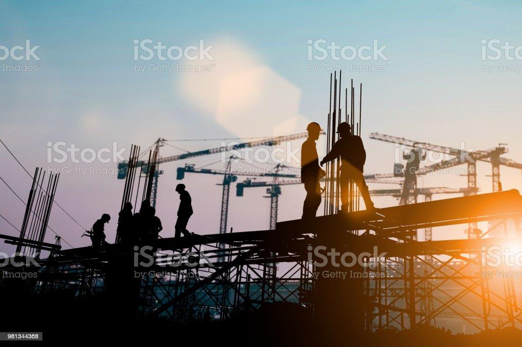 Silhouette der Ingenieur und Bau Team arbeitet am Standort über unscharfen Hintergrund Sonnenuntergang Pastell für Industrie-Hintergrund mit leichten Messe. Erstellen Sie aus mehreren Referenzbildern zusammen. – Foto