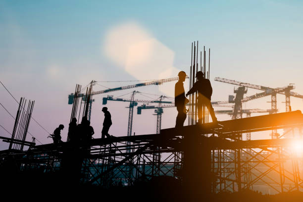 silhouette of engineer and construction team working at site over blurred background sunset pastel for industry background with light fair.create from multiple reference images together. - ingegnere foto e immagini stock
