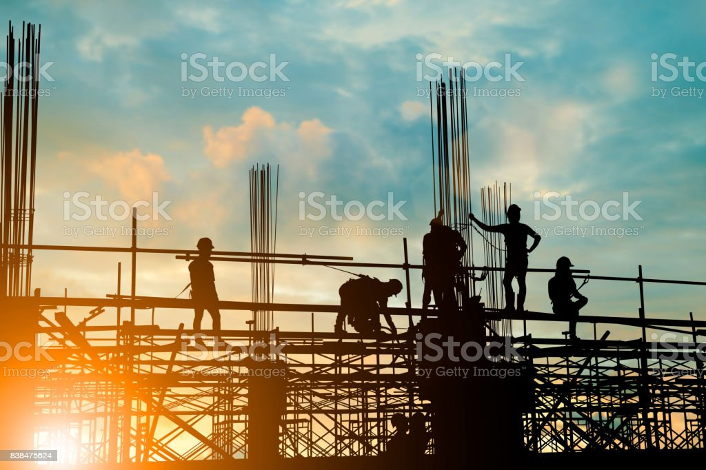 Silhouette of engineer and construction team working safely on scaffolding on high rise building. over blurred background sunset pastel for industry background with Light fair stock photo