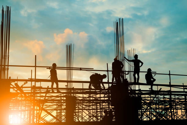 silhouette of engineer and construction team working safely on scaffolding on high rise building. over blurred background sunset pastel for industry background with light fair - vocational training stock photos and pictures