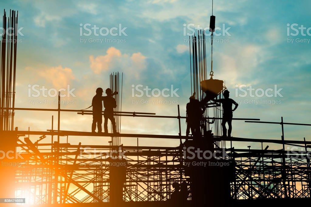 Silhouette der Ingenieur und Bau Team arbeitet sicher Arbeit Last Beton auf Gerüsten am Hochhaus. über unscharfen Hintergrund Sonnenuntergang Pastell für Industrie-Hintergrund mit leichten Messe – Foto