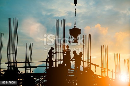 istock Silhouette of engineer and construction team working safely work load concrete on scaffolding on high rise building. over blurred background sunset pastel for industry background with Light fair 838476004