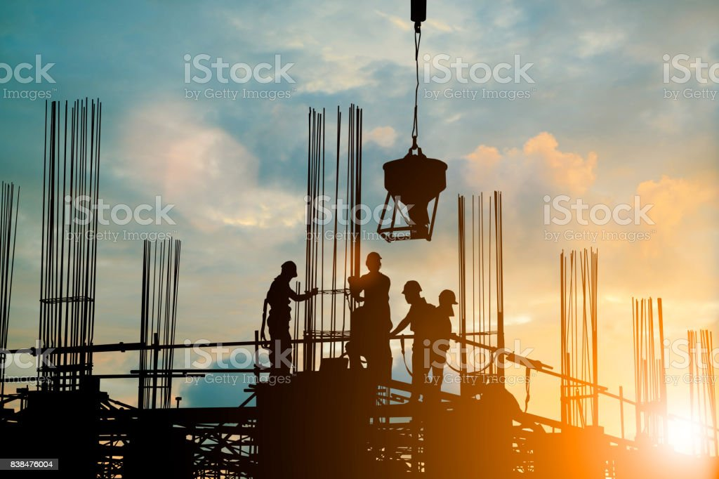 Silhouette of engineer and construction team working safely work load concrete on scaffolding on high rise building. over blurred background sunset pastel for industry background with Light fair - foto stock