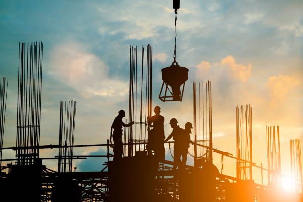Silhouette of engineer and construction team working safely work load concrete on scaffolding on high rise building. over blurred background sunset pastel for industry background with Light fair stock photo