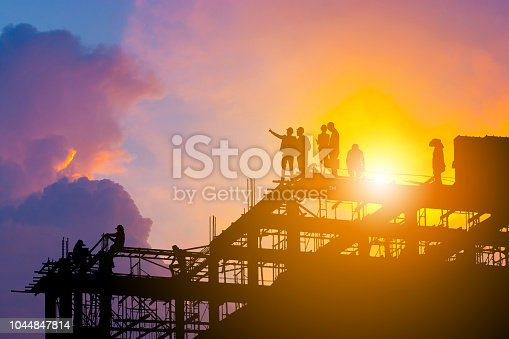 istock Silhouette of Engineer and worker on building site, construction site with clipping path at sunset in evening time. 1044847814