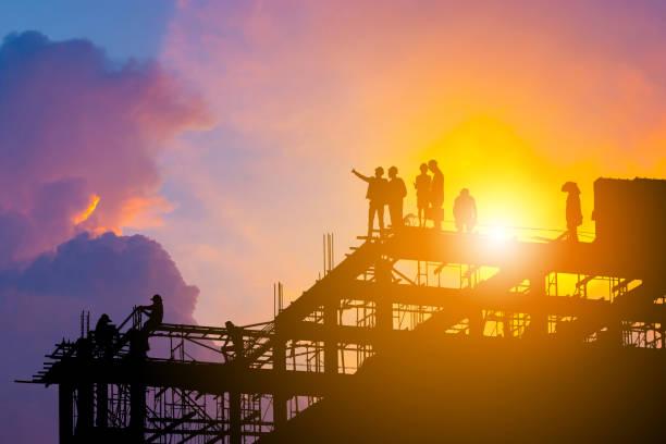 silhouet van ingenieur en werknemer op de bouwplaats, bouwplaats met uitknippad bij zonsondergang in de avond van de tijd. - toren bouwwerk stockfoto's en -beelden