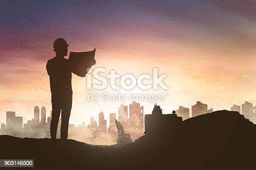 istock Silhouette of engineer man looking his blueprint in construction site 903146500