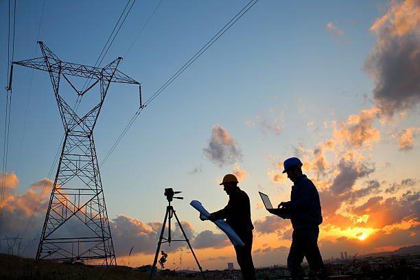 silhouette of engineers workers at electricity station - transmission lines stock photos and pictures