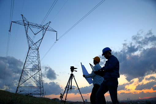 Silhouette of engineers workers at electricity station.