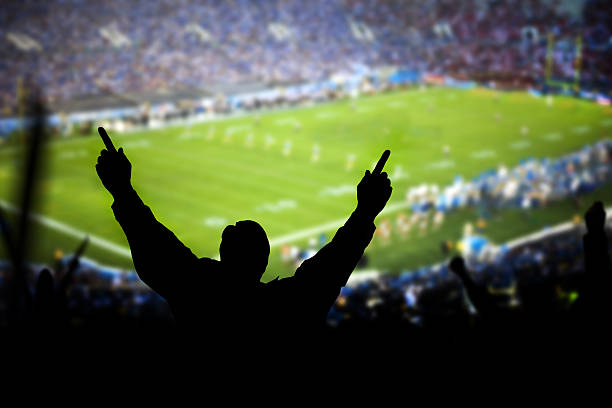 Silhouette of excited fans at football game stock photo