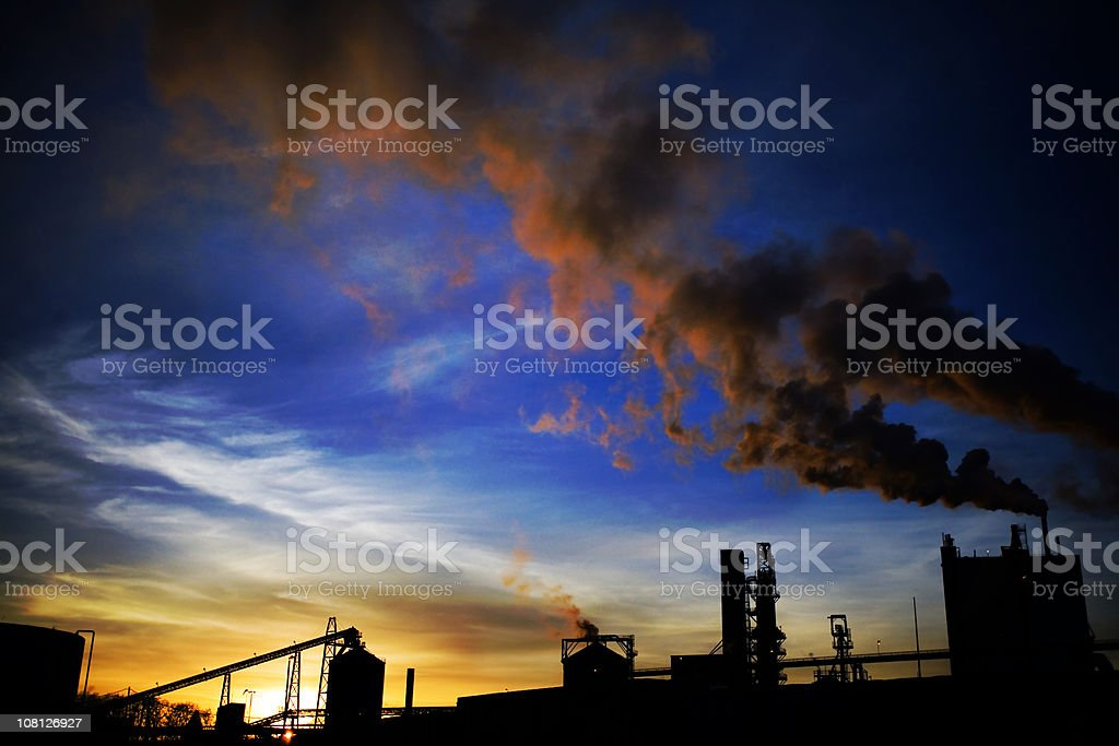 Silhouette of Factory and Smoke at Sunset royalty-free stock photo
