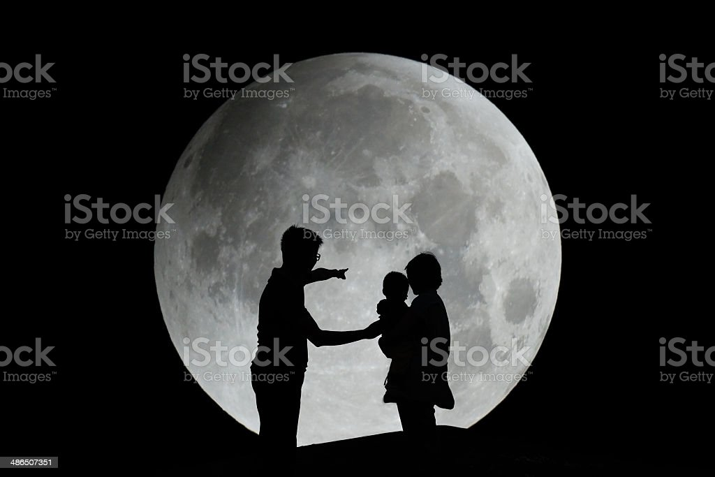 Silhouette of family with moon stock photo