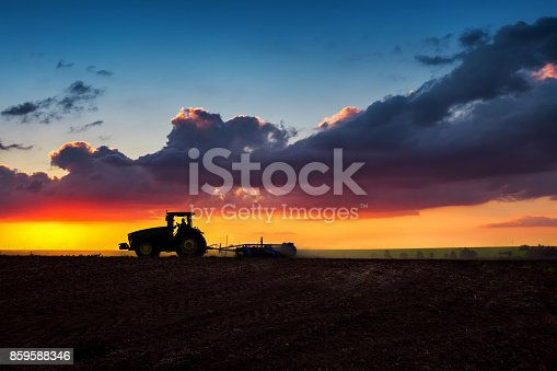 Farmer in tractor preparing land with seedbed cultivator, sunset shot. Silhouettes.