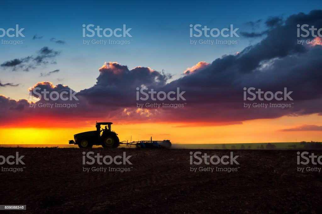 Silhouette of Farmer in tractor preparing land with seedbed cultivator, sunset shot stock photo