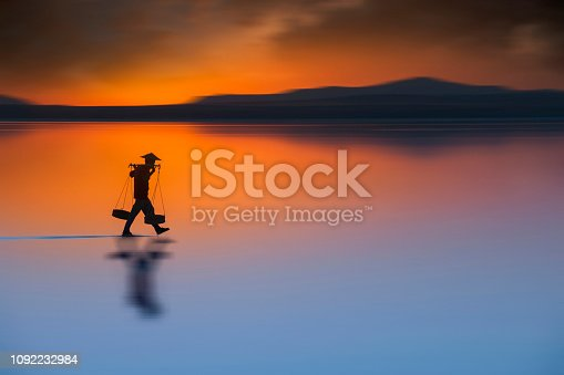 istock Silhouette of farmer walking and carrying salt and backing to home at nightfall. Travel landscapes and destinations 1092232984