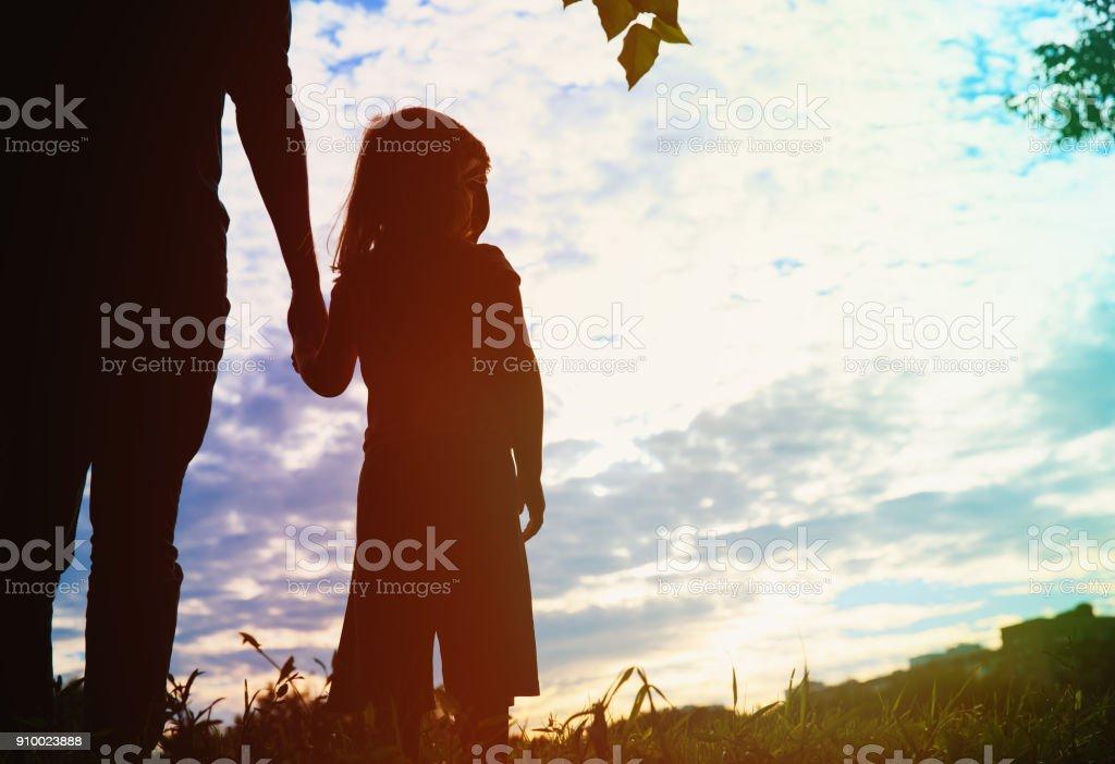 のシルエット父と娘手をつなぐ日没に ストックフォト