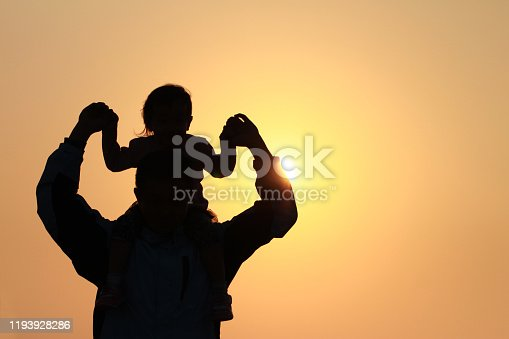 silhouette of father and daughter under sunset. background for father's day and happy family.