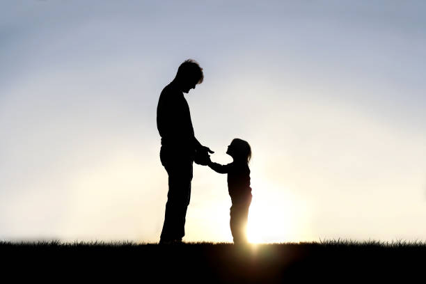 Silhouette of Father and his Happy Little Child Holding Hands and Smiling at Eachother Outside stock photo