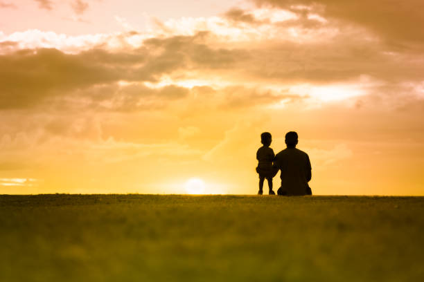 Silhouette of father and his little boy watching the sunset. stock photo
