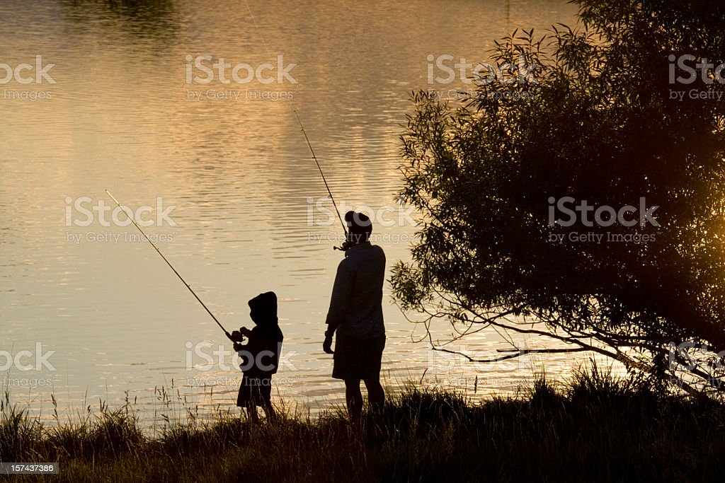 Silhouette of father and son fishing on a lake stock photo