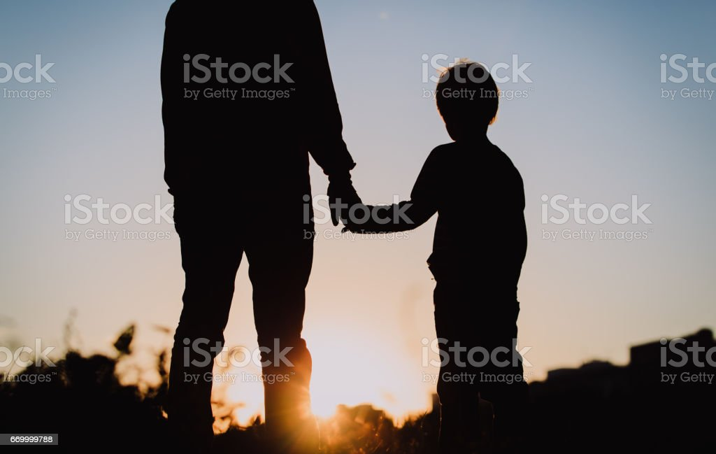 silhouette of father and son holding hands at sunset stock photo