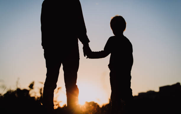 のシルエットを父と息子に手をつなぐ夕暮れ - 息子 ストックフォトと画像