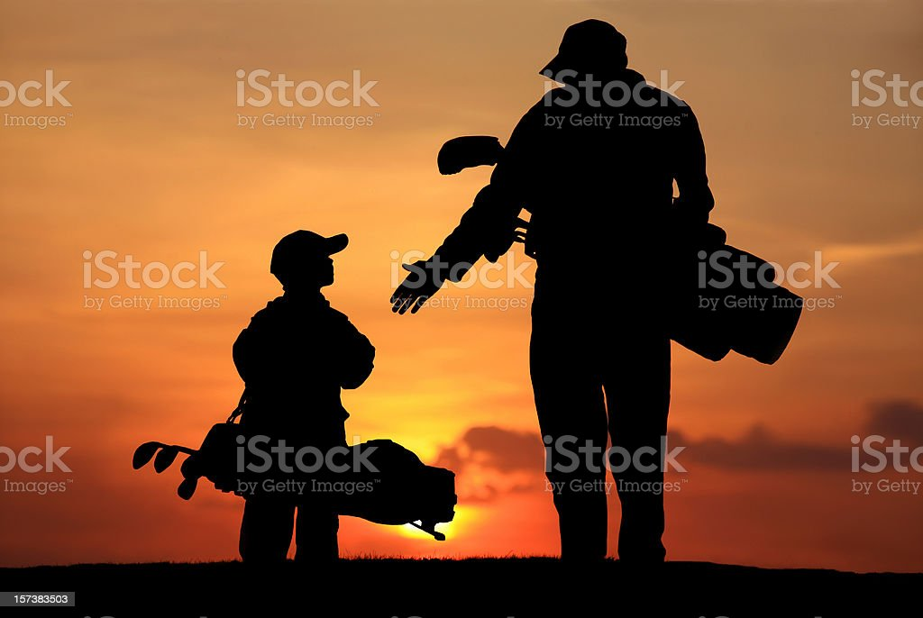 Silhouette of Father and Son on the Golf Course stock photo