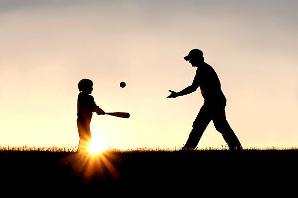 Silhouette of Father and Son Playing Baseball Outside A silhouette of a father and his young child playing baseball outside, isolated against the sunsetting sky on a summer day. baseball sport stock pictures, royalty-free photos & images