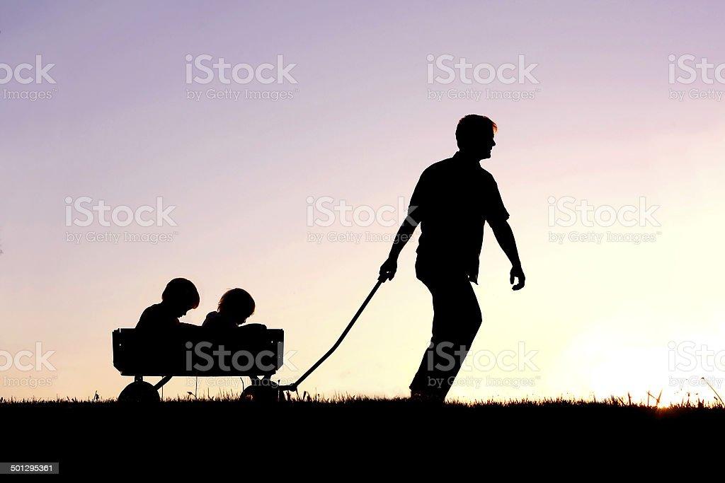 Silhouette der Vater ziehen Sons in Wagon bei Sonnenuntergang – Foto