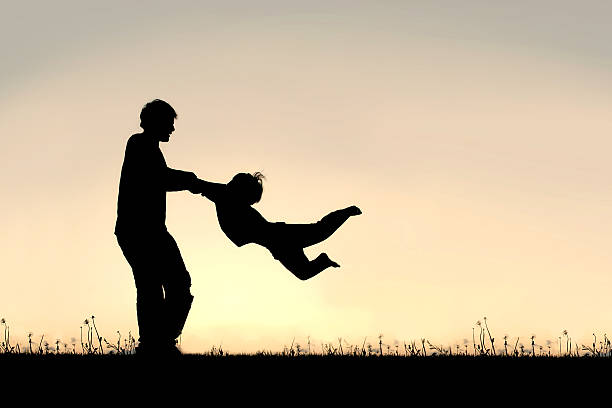 Silhouette of Father Spinning CHild Around Outside stock photo