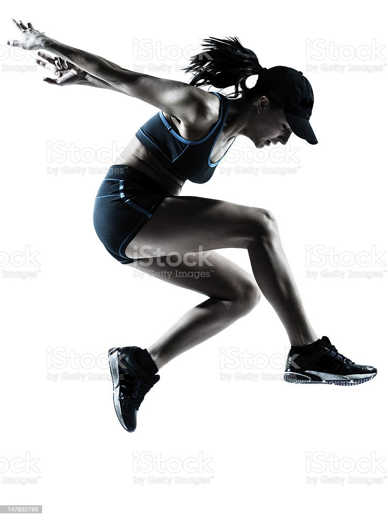 Silhouette of female athlete landing from a jump stock photo