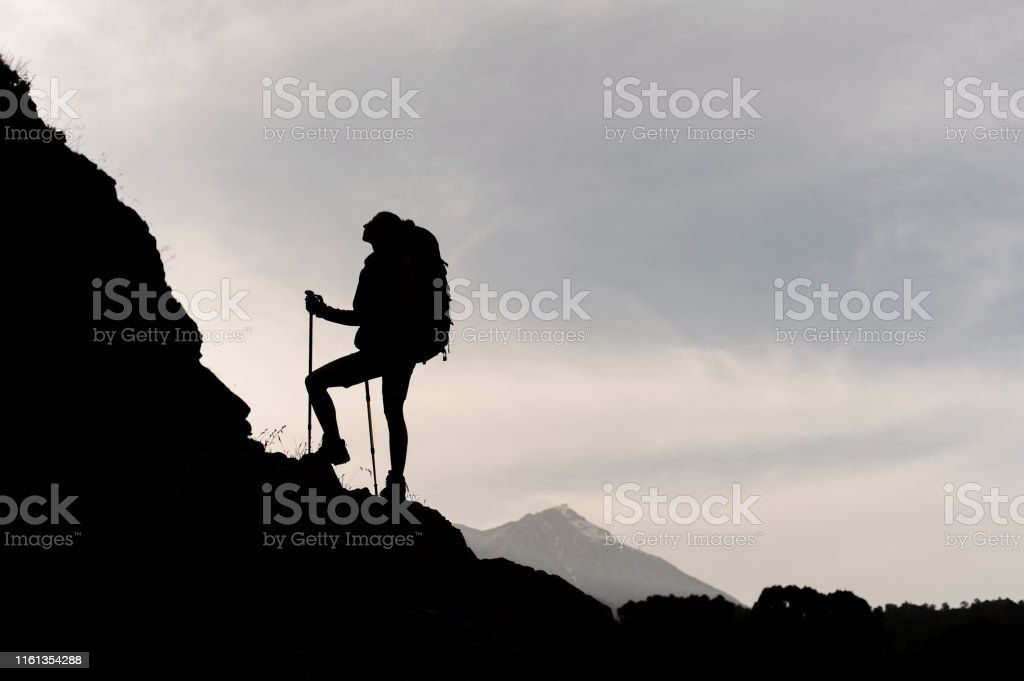Silhouette of female hiker with sticks and backpack climbing on...
