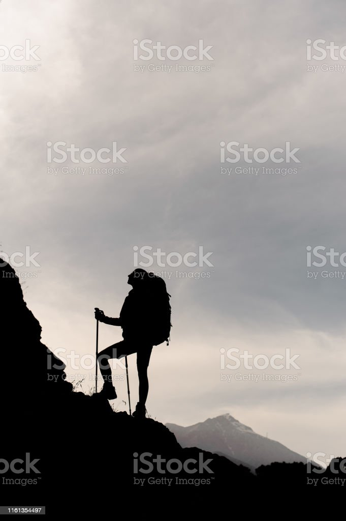 Silhouette of female hiker with sticks and backpack climbing up...