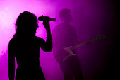 Silhouette of female holding microphone in purple light