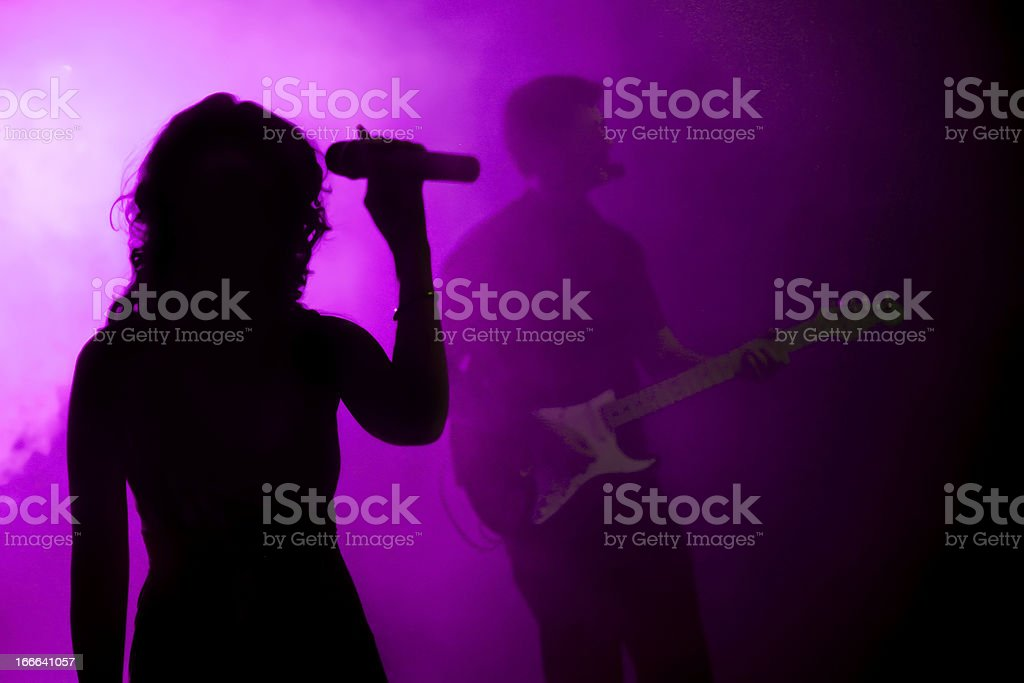 Silhouette of female holding microphone in purple light stock photo