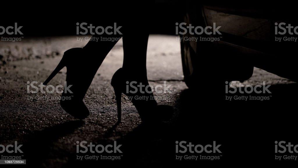 Silhouette des weiblichen Beine in Highheels ans Auto, Prostitution, Sextourismus – Foto