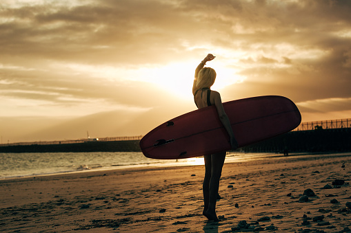 Silhouette Of Female Surfer Posing With Surfboard At Sunset With Backlit - zdjęcia stockowe i więcej obrazów Deska surfingowa