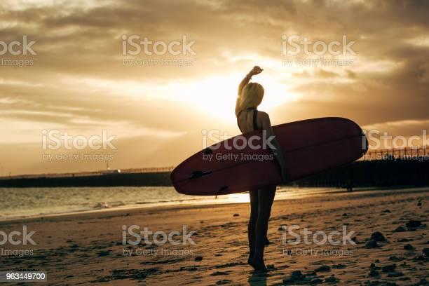 Sylwetka Surferki Pozującej Z Deską Surfingową O Zachodzie Słońca Z Podświetlenia - zdjęcia stockowe i więcej obrazów Deska surfingowa