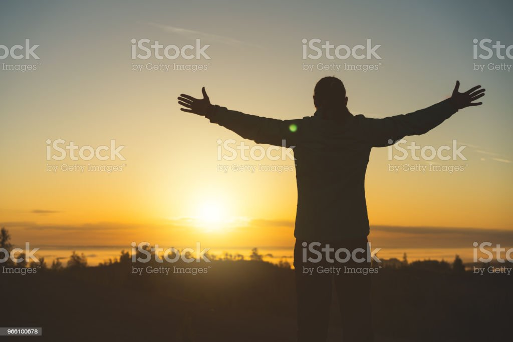Silhuetten av kvinnliga resenären på toppen av berget vid solnedgången - Royaltyfri Andlighet Bildbanksbilder