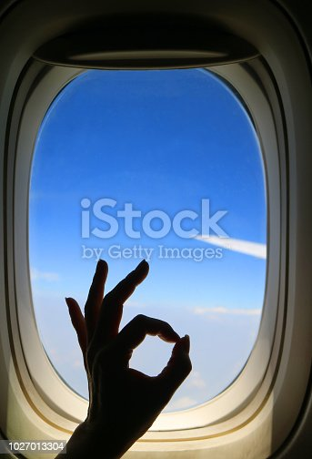 Silhouette of female's hand posing OK sign against airplane window with vibrant blue sky and airplane wing during her happy flight