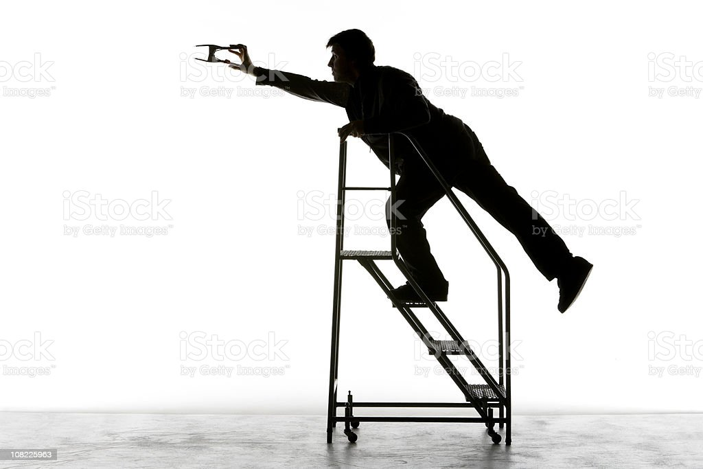 Silhouette of Film Technician on Staircase Holding Metal Clip stock photo