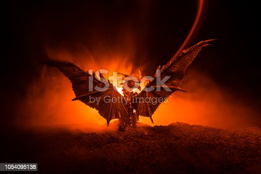 Silhouette of fire breathing dragon with big wings on a dark burning fire background. Selective focus